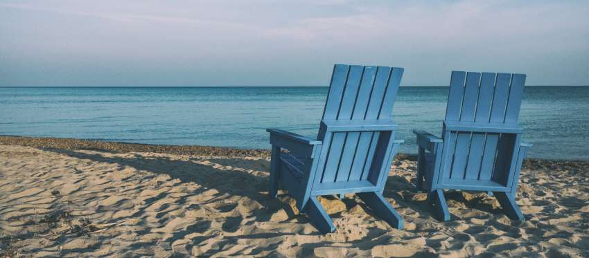 Two blue chairs on a beach facing the ocean.