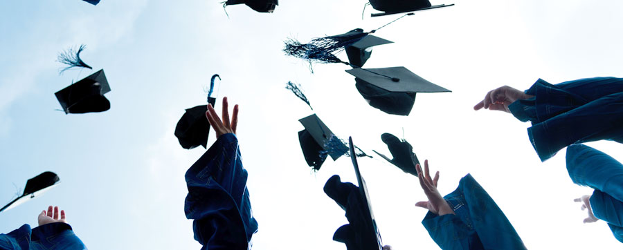Graduates throwing their caps into the air.