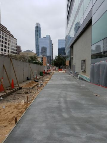 Freshly poured sidewalk on Colorado Street will be lined on the left by tree grates, trees, and benches.  Framing for the remainder of the curtainwall system has already been installed on the building.