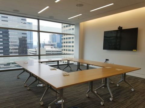 Tables and monitor have been installed in a medium conference room.